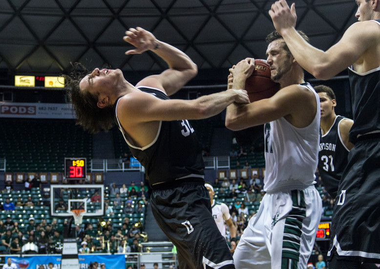 University of Hawaii forward Gibson Johnson, right, defends agaists Davidson's guard Rusty Reigel, left during a Diamond Head Classic Match between University of Hawaii and Davidson on December 24, 2017.