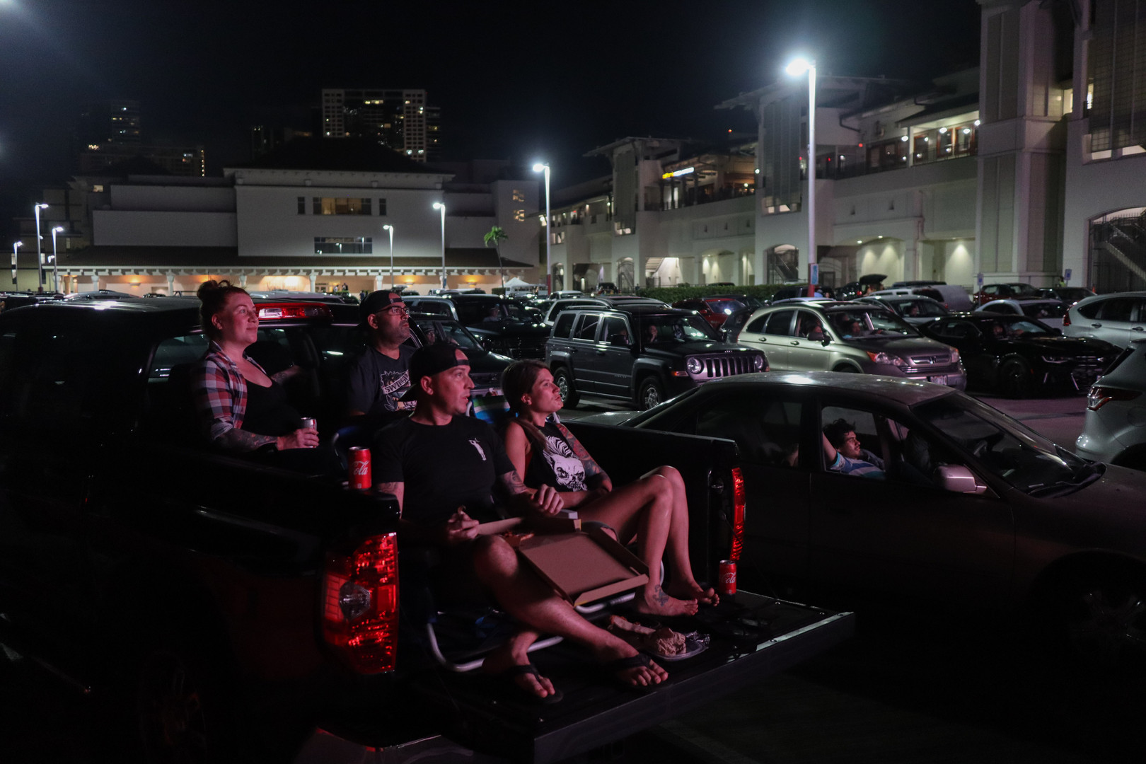 Todd Week, Casey Week, Jen Valles, Marc Valles enjoys the movie from their truck in a drive-in movie by Aloha Drive-In Movies at Ala Moana Center on October 30, 2020. Aloha Drive-In movies in partnership with Hawaii International Film Festival transformed the parking section between Neiman Marcus and Macy's at Ala Moana Center into an outdoor theater. The viewing space feature a 30-foot LED screen, with enough space to fit 83 vehicles, socially distanced.