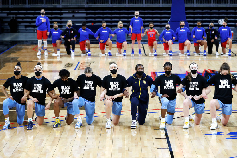 Players of Marquette, foreground and DePaul women's basketball team kneel during the national anthem before an NCAA college basketball game between Marquette and DePaul on Wednesday, Feb. 24, 2021, in Chicago. (AP Photo/Shafkat Anowar)