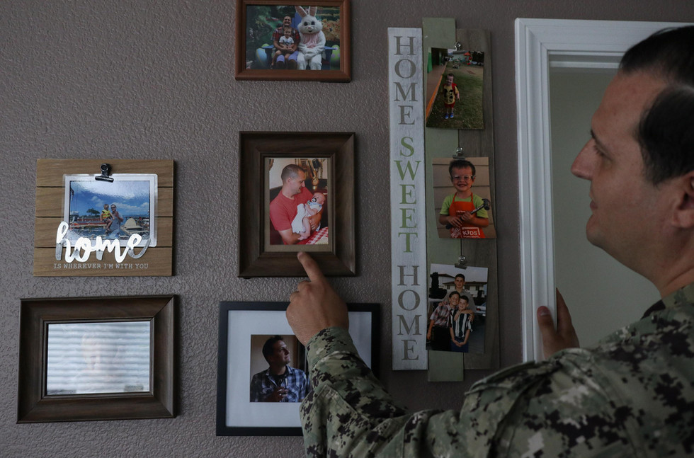 Stremel points to an older framed photo of him holding his son, Calvin when he was about nine months old at his home in Wai'anae, Hawai'i.