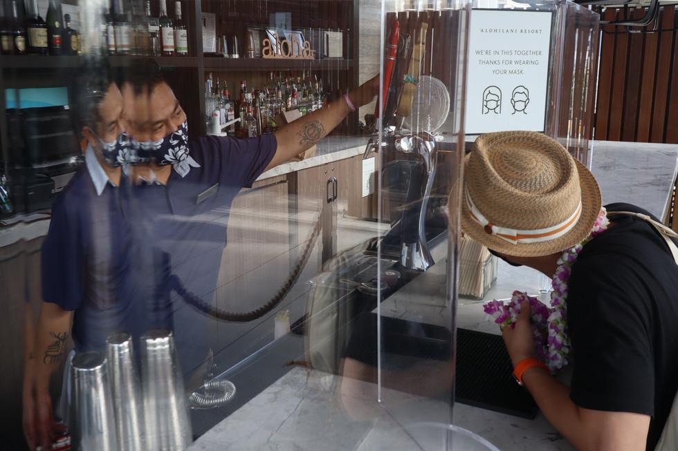 'Alohilani Resort bartender converses with a customer on November 20, 2020.