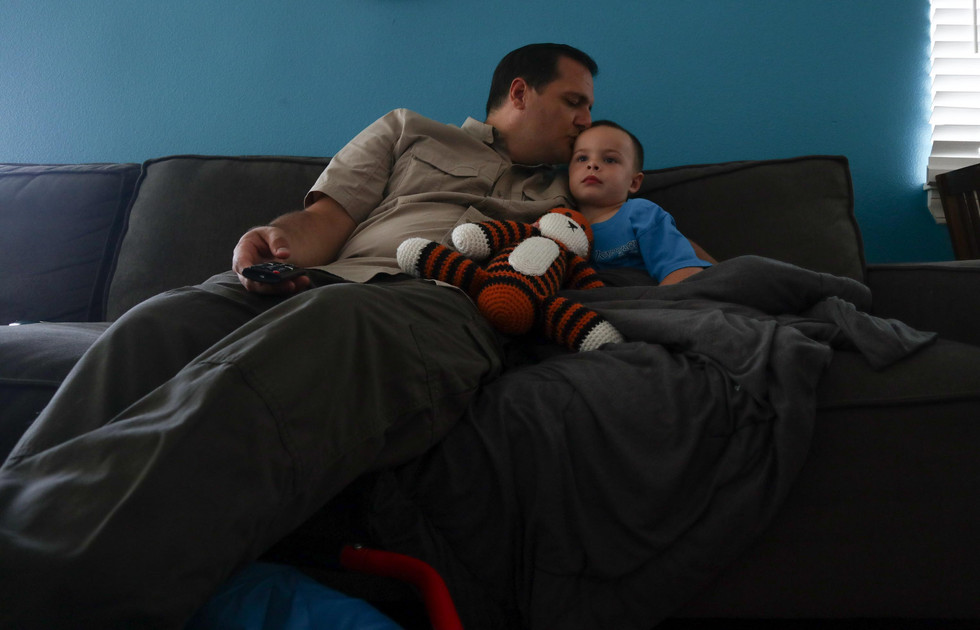 Father and son spends time on the living room couch while they watch TV.