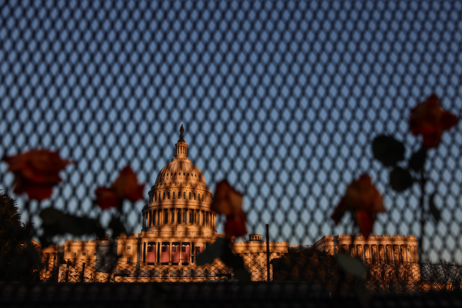 The U.S Capitol seen through the steel fence and roses placed by the ongoing visitors as it prepares for the presidential inauguration on January 20, 2021.