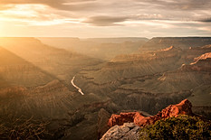 Golden rays of light shining down into the Grand Canyon at sunset.