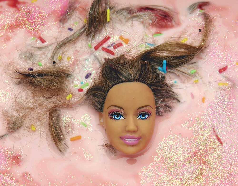 """""""I've put the Barbies head in a pink liquid - The pink liquid symbolizes femininity, the Barbie dolls head is almost 'drowning in her own femininity'."""" By Janisha Patel"""