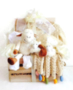 Organic baby clothing and plush lamb in natural wodden crate