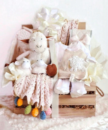 New baby twins wood crate filled with organic cotton wearables and various baby gifts.