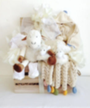 Wooden crated filled with organic cotton wearables and plush gifts for the new baby boy