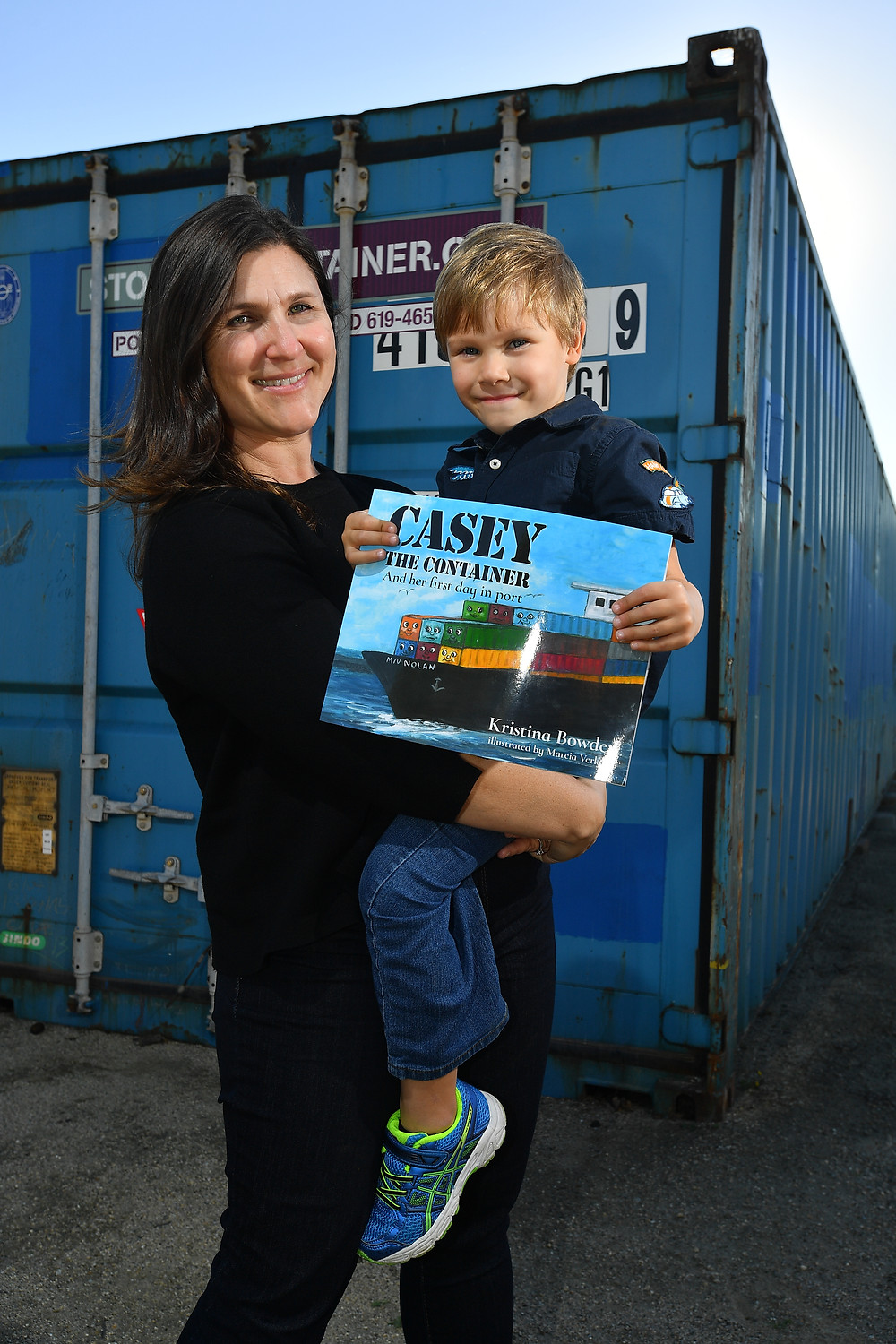 """Author Kristina Bowden and her son in front of a container known as """"Big Blue"""""""