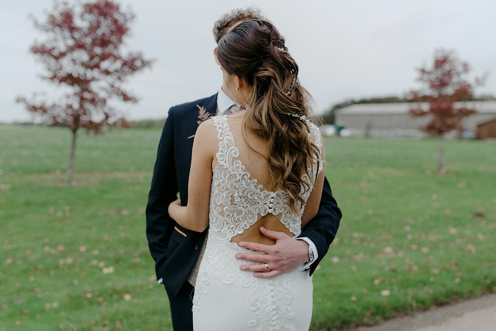 grooms hand on brides back outdoor wedding
