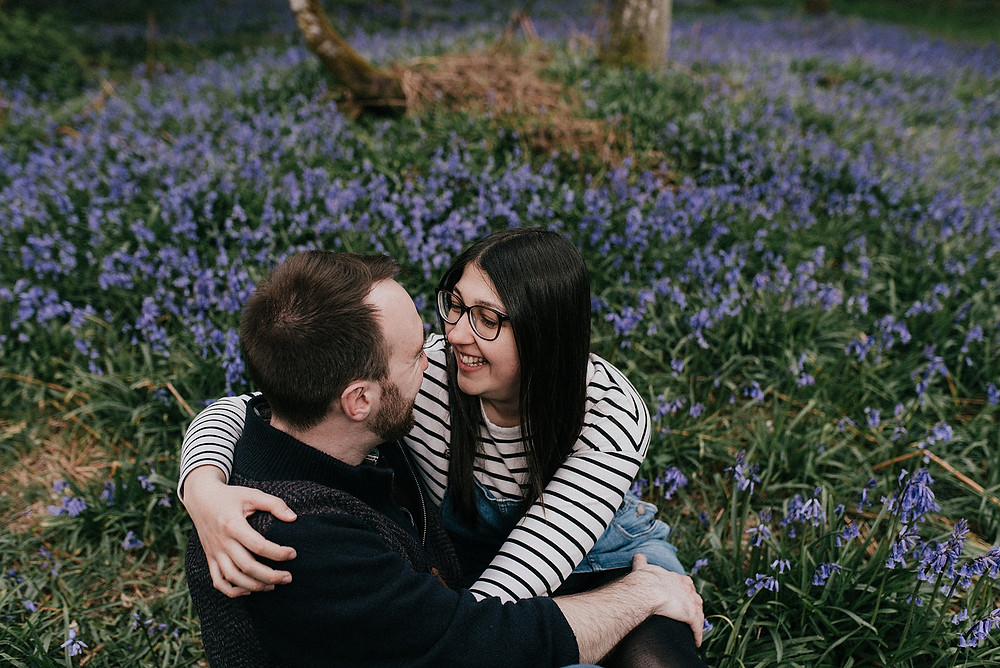cute couple sat down in bluebells