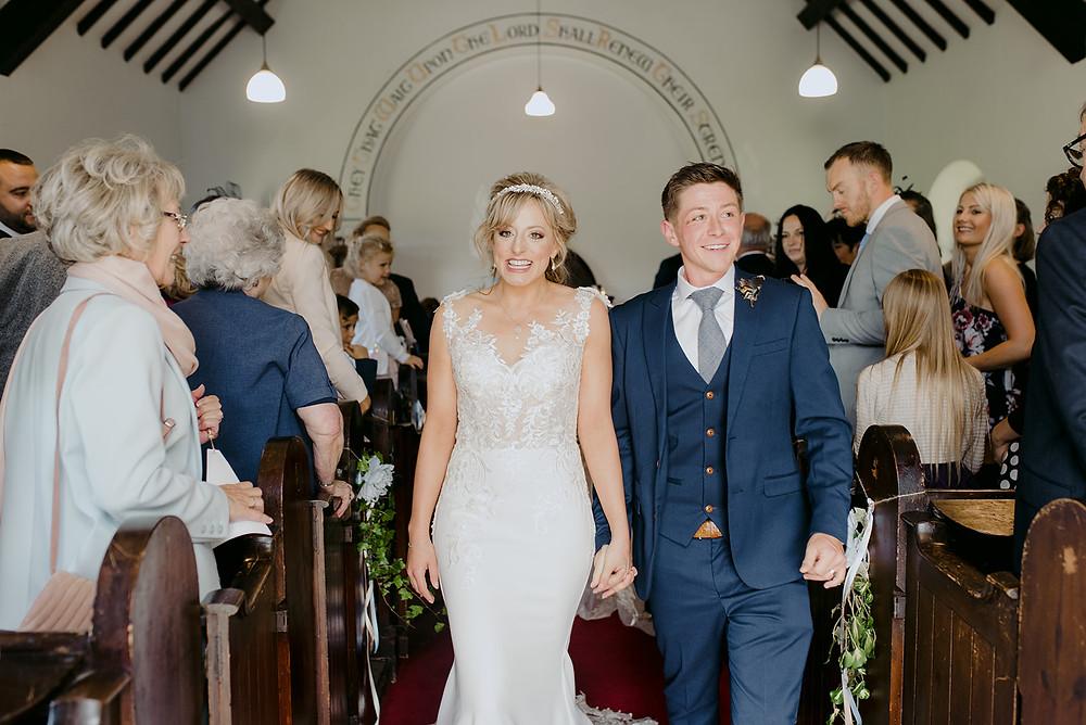 bride and groom leaving chapel just married