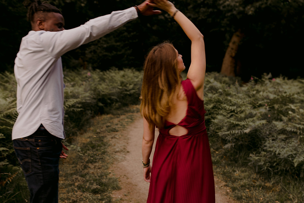 natural photo of couple twirling in woodland
