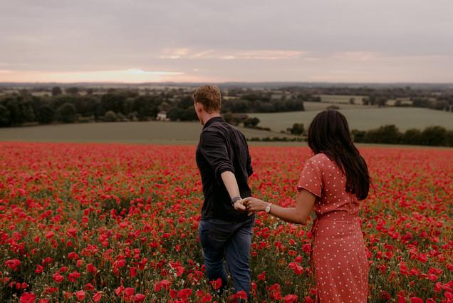 guy leading girl through poppy field