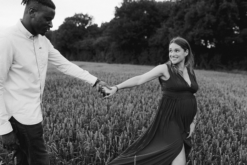 outdoor photoshoot of couple and bump in field