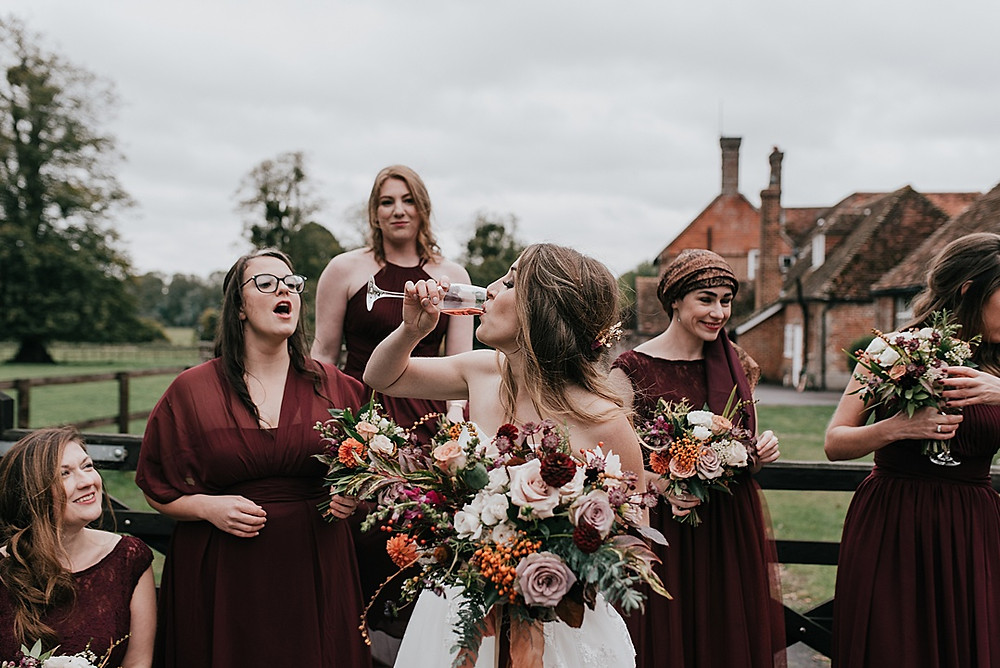 bride downing prosecco with bridesmaids