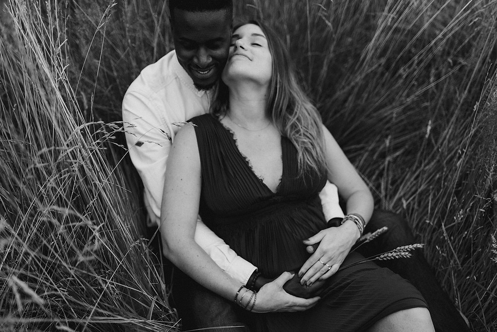 black and white photo of couple laying in long grass