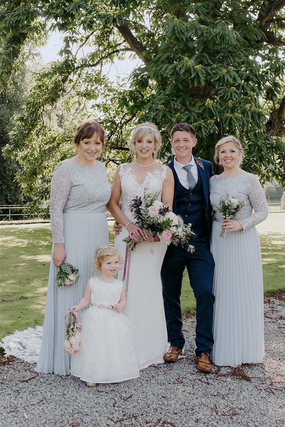 wedding group shot outdoor by tree sunny