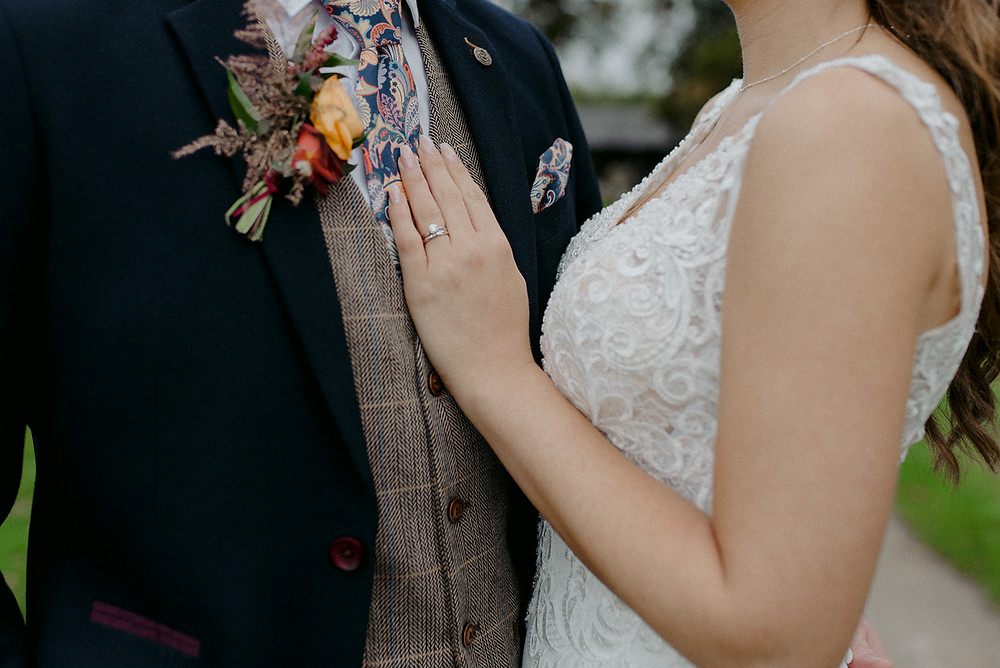 close up of brides hand and rings on grooms chest
