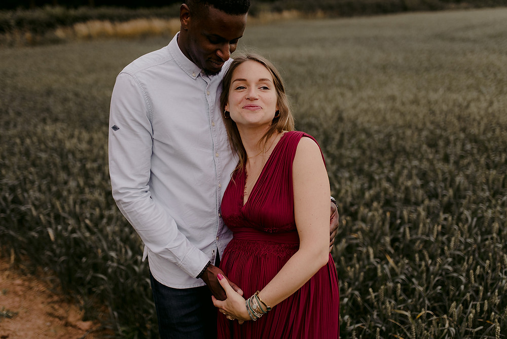 pregnant photoshoot in red dress in field