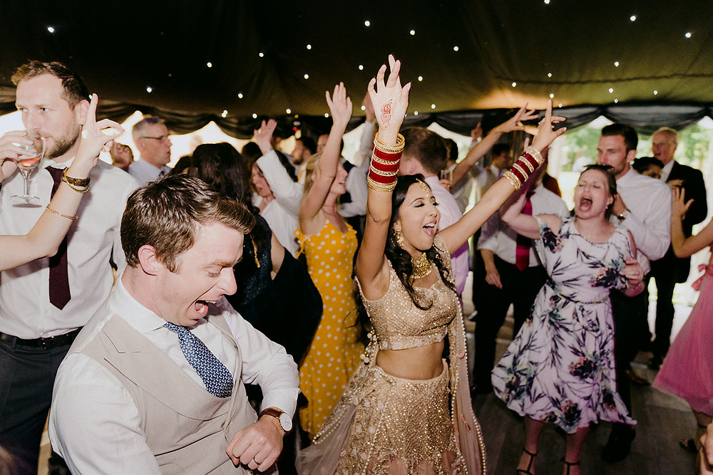 bride with arms in the air on wedding dance floor