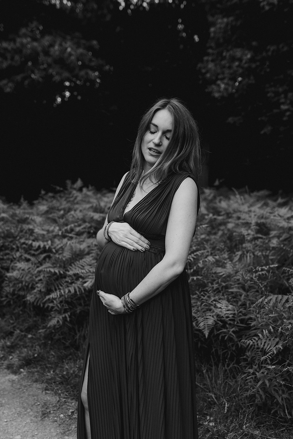 black and white photo of pregnant women in woods