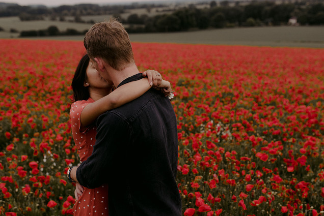 couple kissing in poppy field photographer