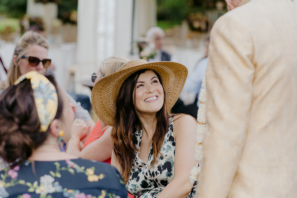 smiling wedding guest in hat