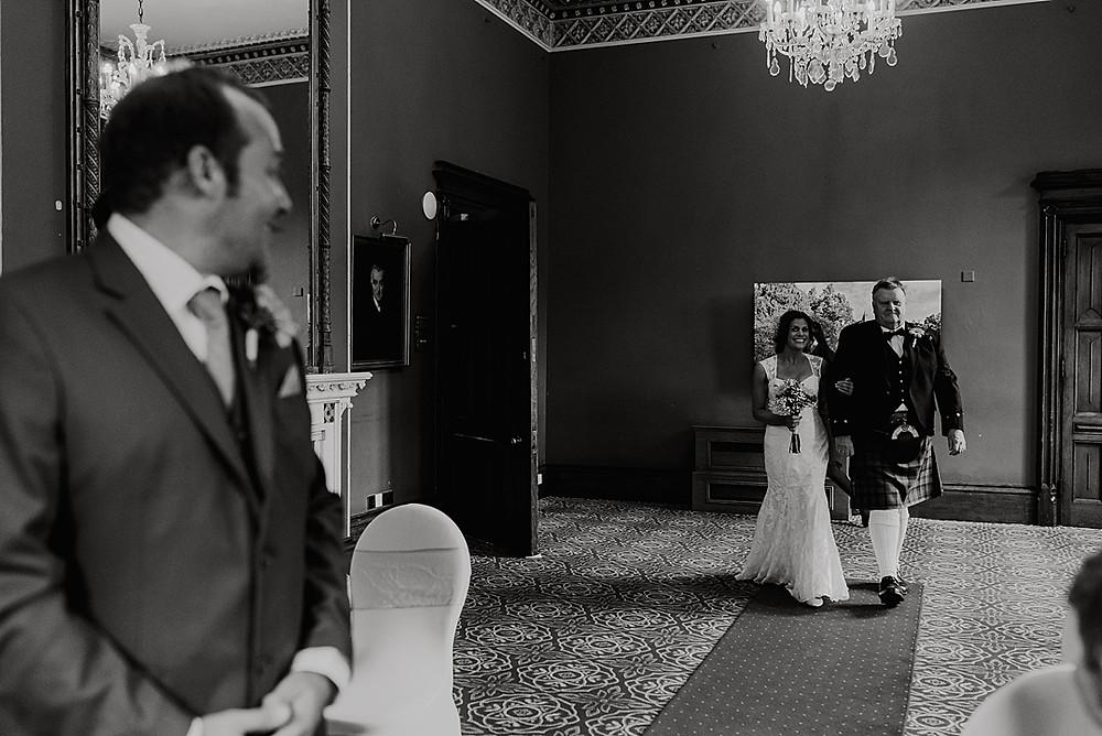 groom sees bride walking down the aisle