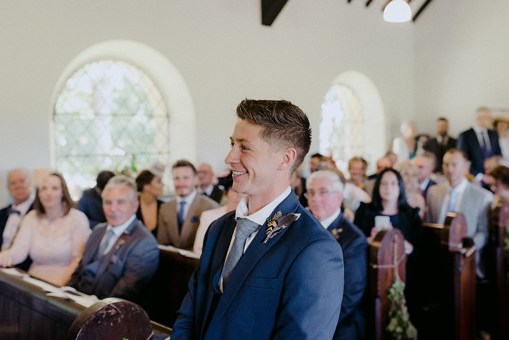 groom smiling waiting for groom in chapel