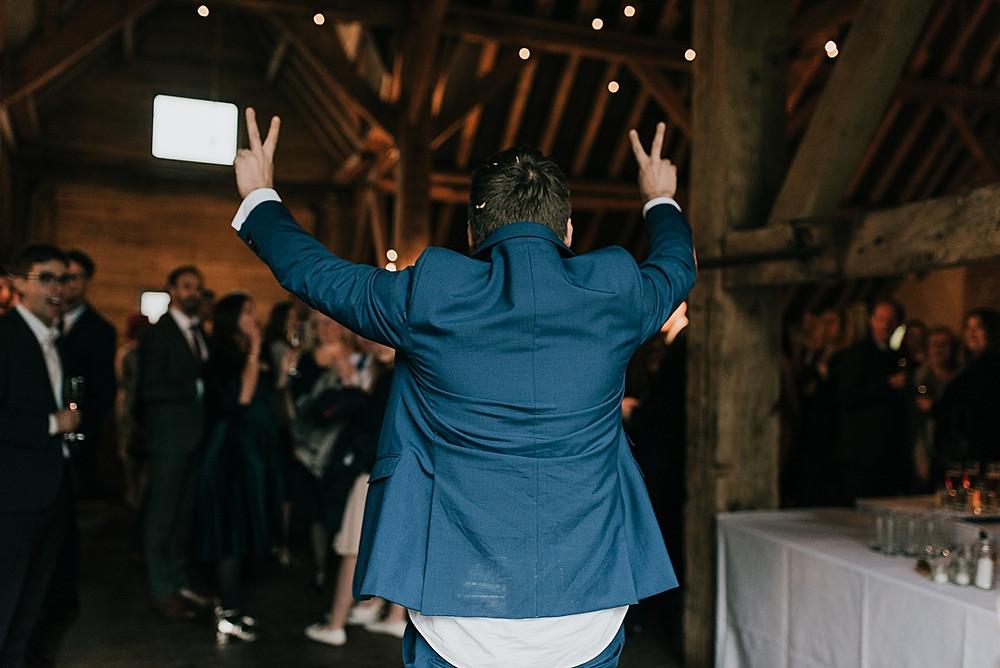 groom entering wedding reception
