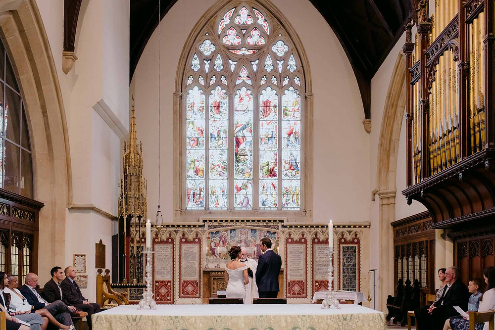 wide shot of wedding in church stained glass window