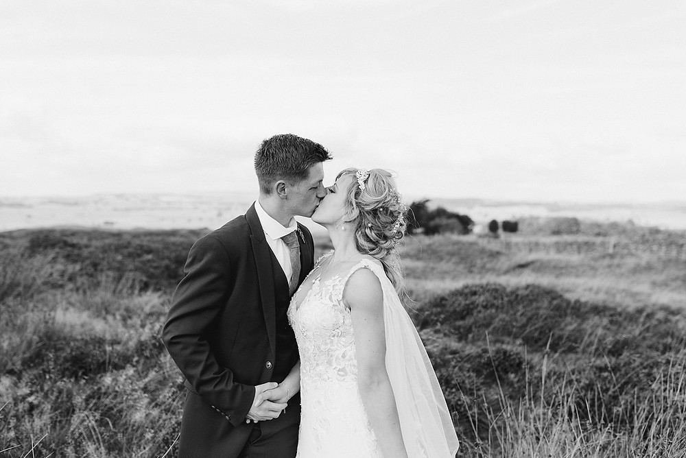 black and white photo of bride and groom kissing outdoors