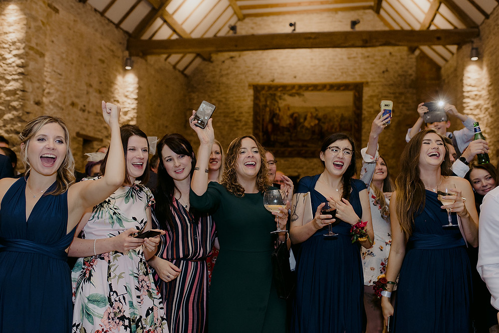 guests cheering at wedding cake cutting