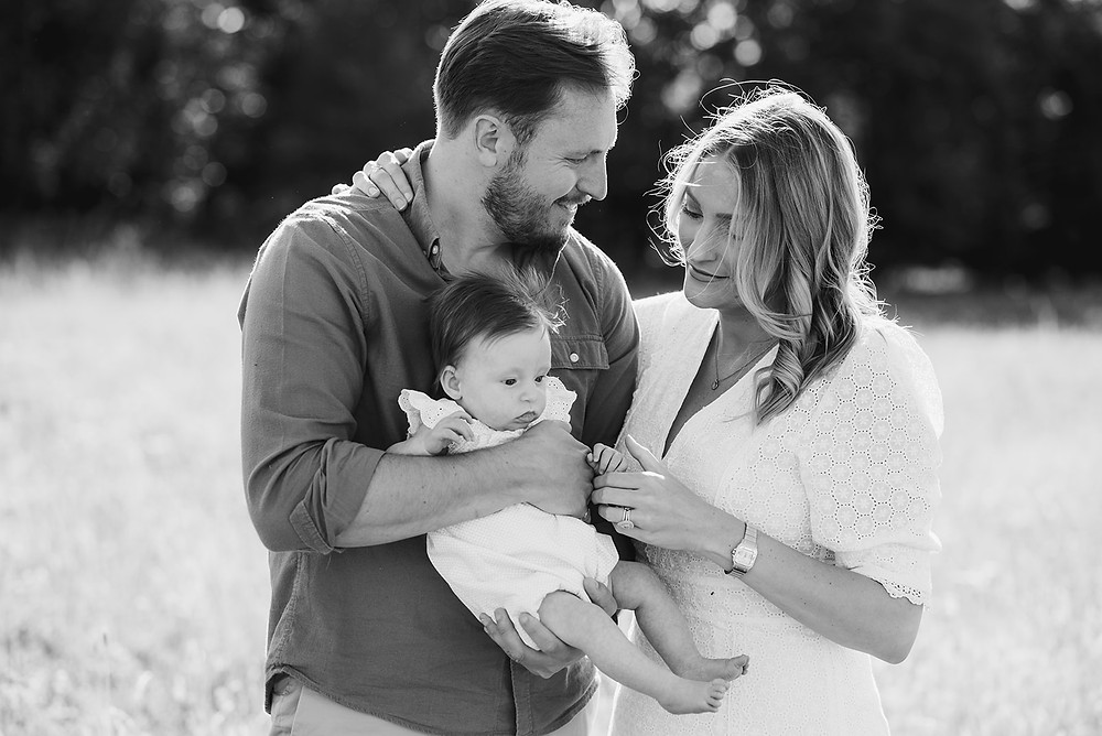 black and white photography of family with newborn