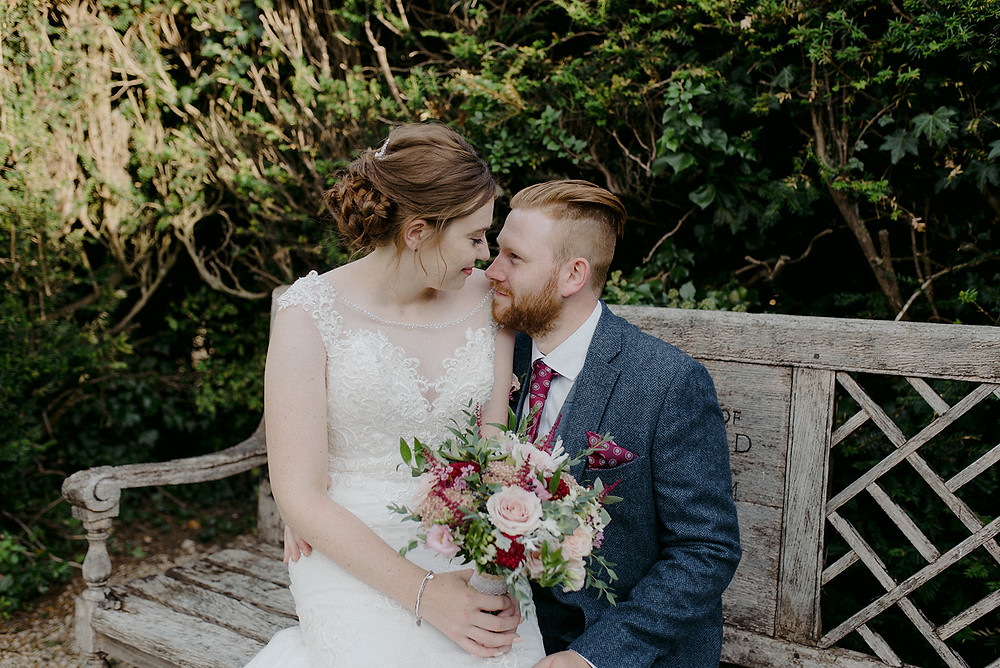 bride and groom sitting on park bench