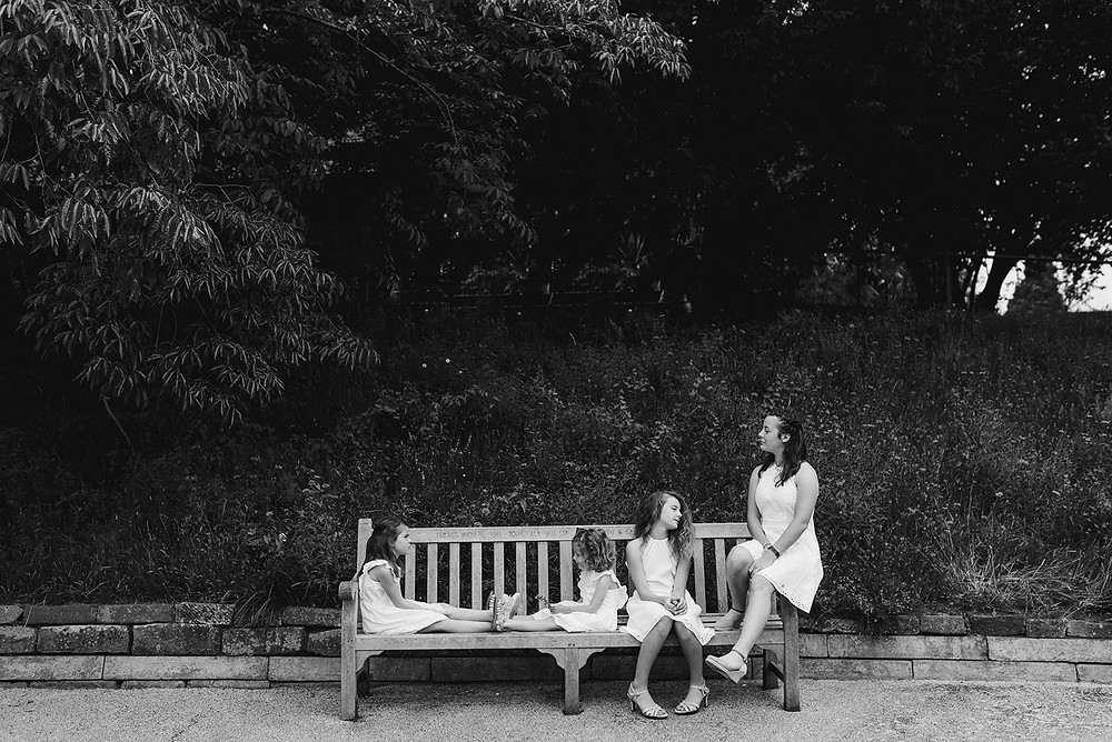 four girls sitting on a bench in park