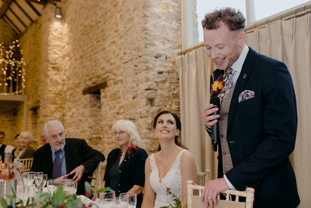 groom giving wedding speech and bride smiling