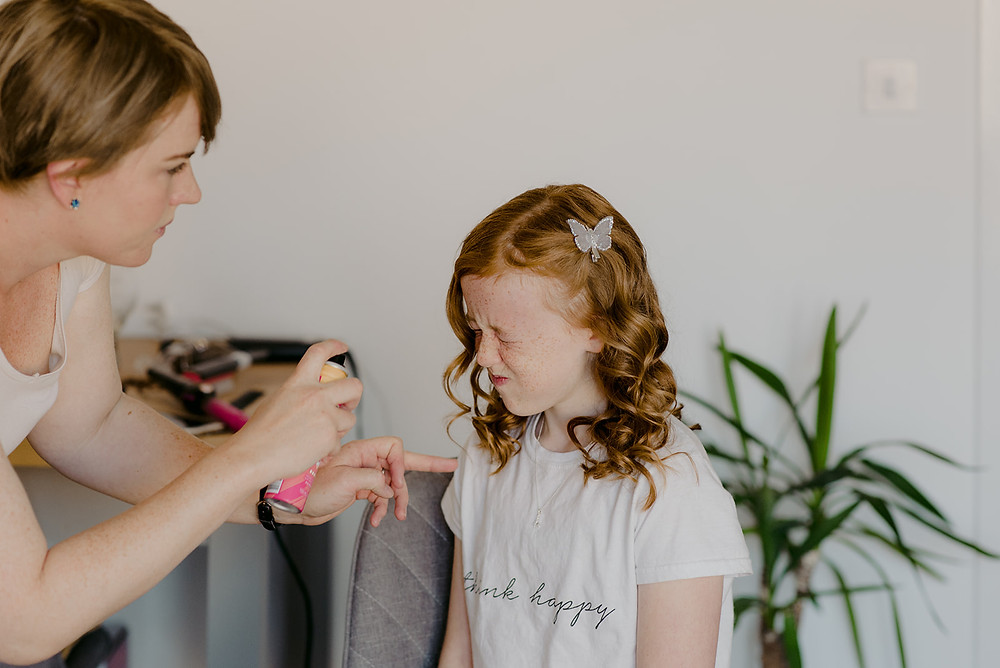 flower girl getting hair done on wedding morning