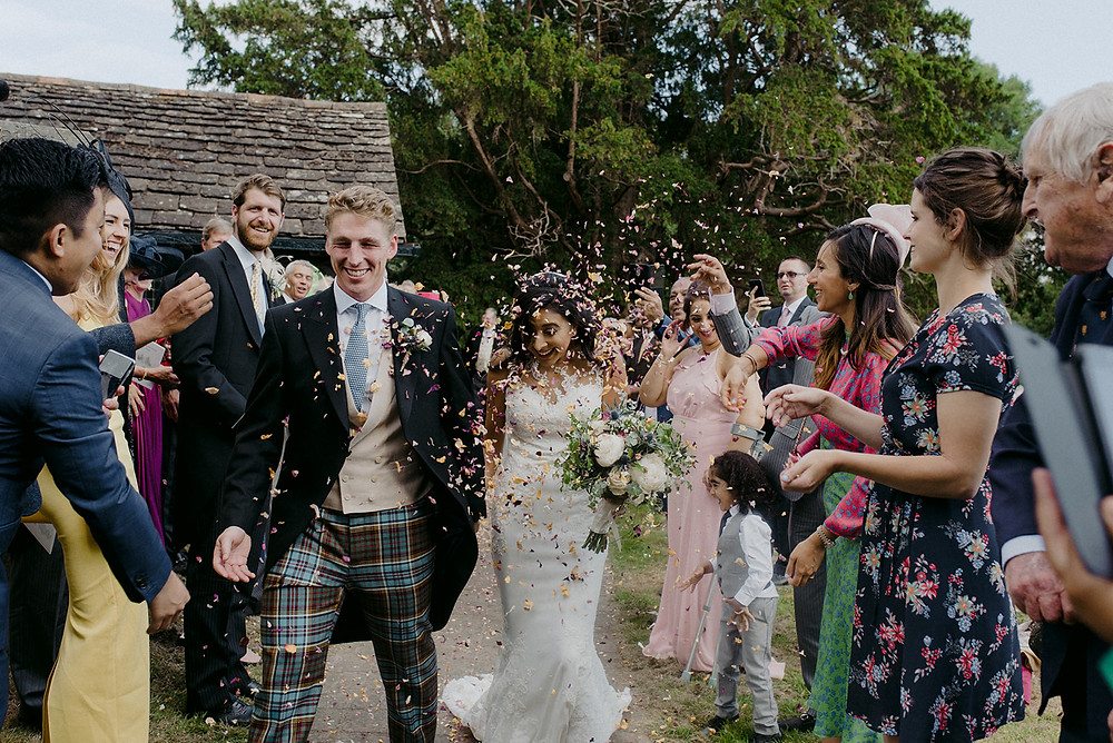 bride and groom confetti shower outside church