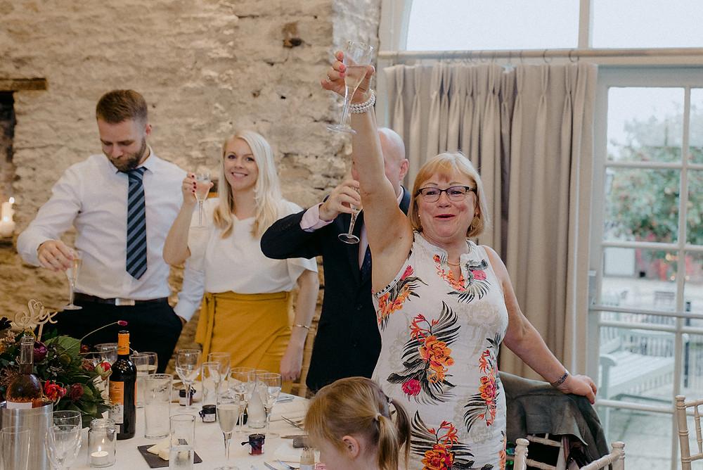 raising champagne glasses at wedding speech