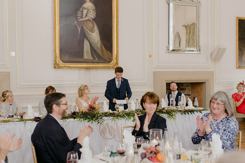 groom giving speech and bride clapping