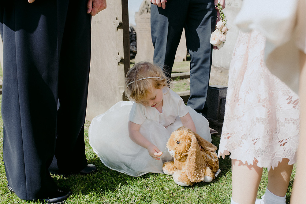 little flower girl in white dress on lawn