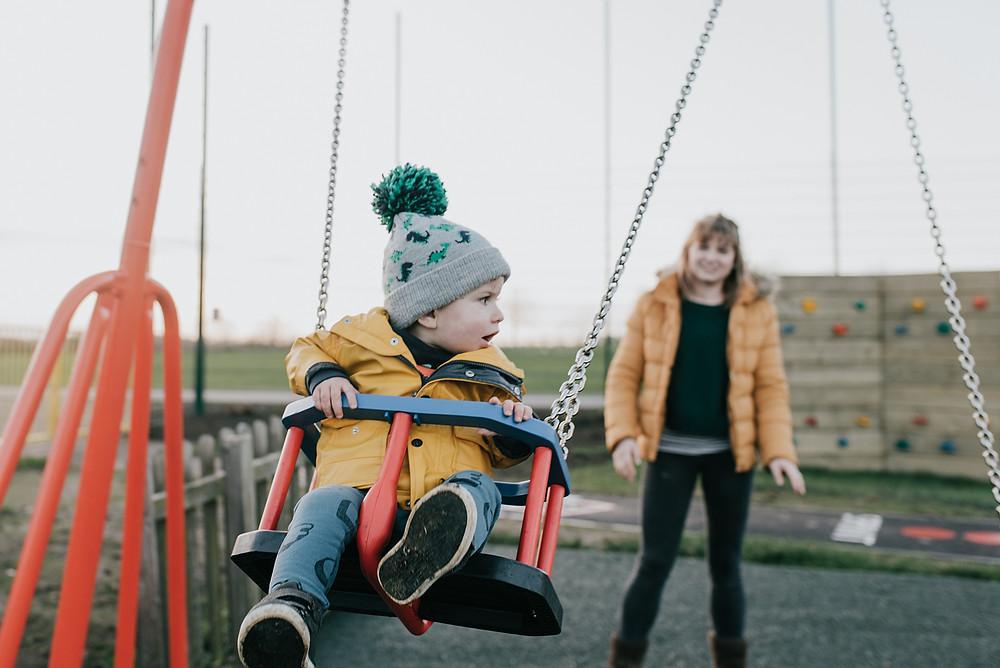 boy on swing in bobble hat