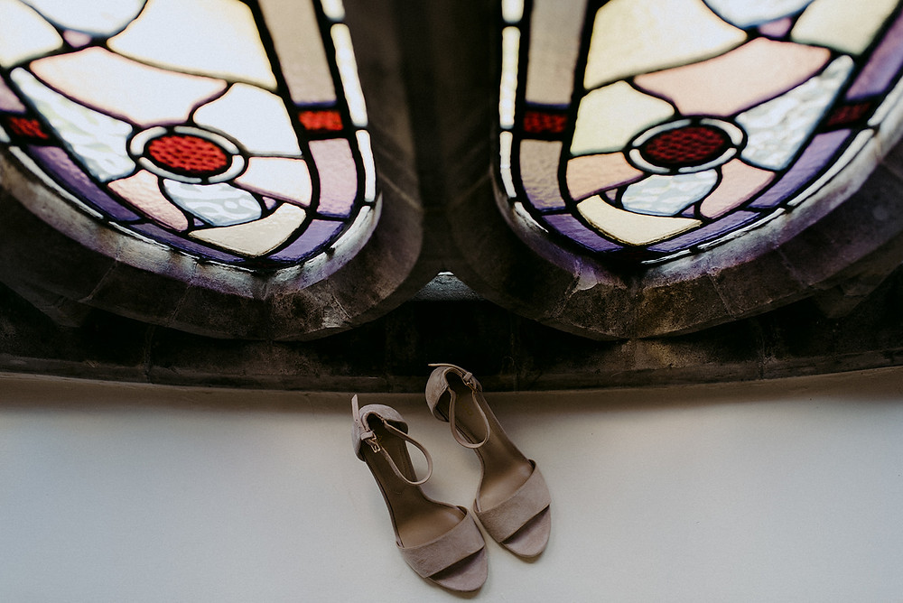 bridal nude sandals by stained glass window