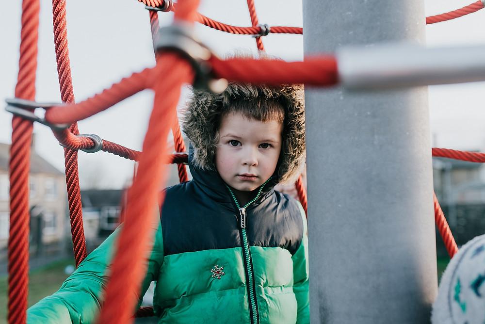 boy on climbing frame natural portrait