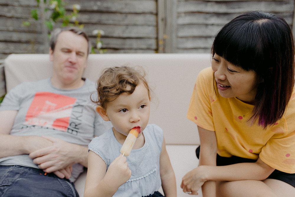 family with little girl eating lolly