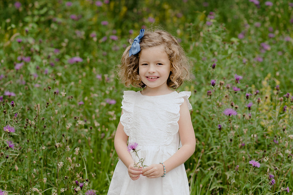 little girl holding flower in wild flower meadow