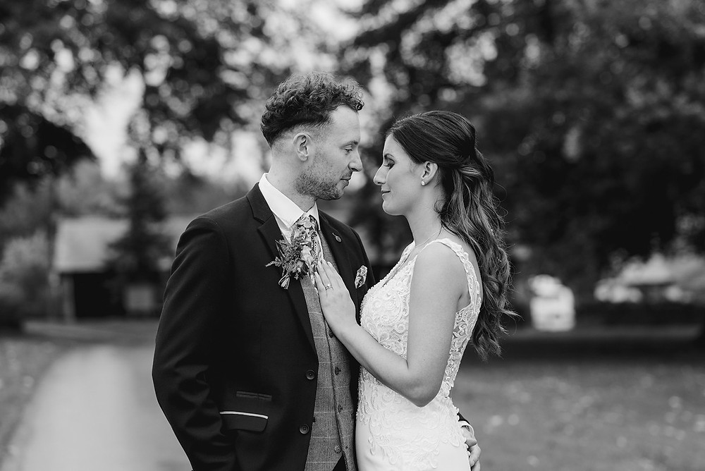 black and white image of wedding couple facing each other