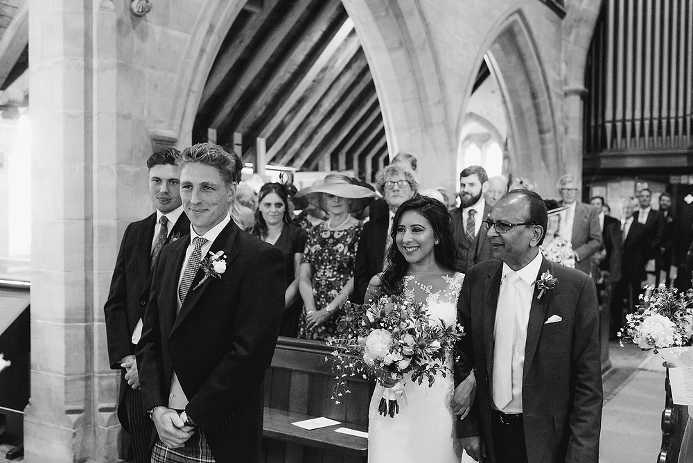black and white photo of bride and groom at alter